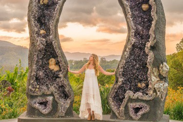 Woman in white dress stands between two tall amethyst crystals in NSW